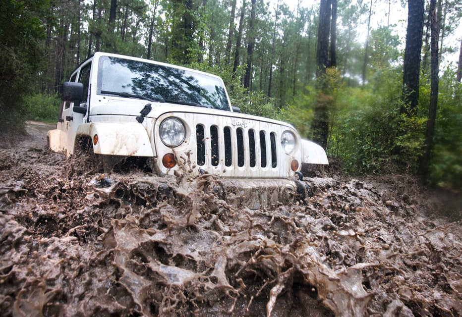 White jeep off roading through mud
