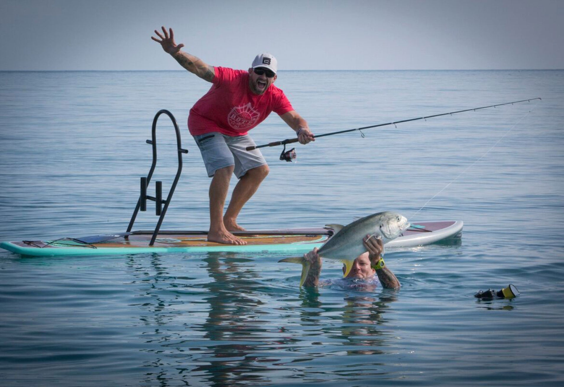 Sean Murphy holding up catch caught from a BOTE paddle board