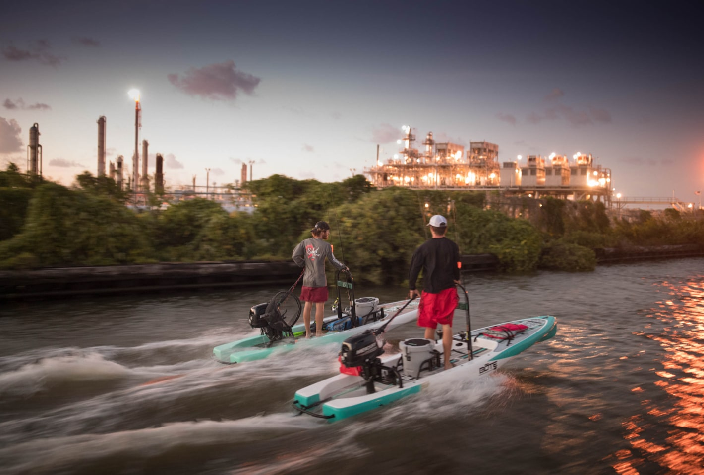 Red and Brown Frenette riding their BOTE Rover microskiffs next to refineries