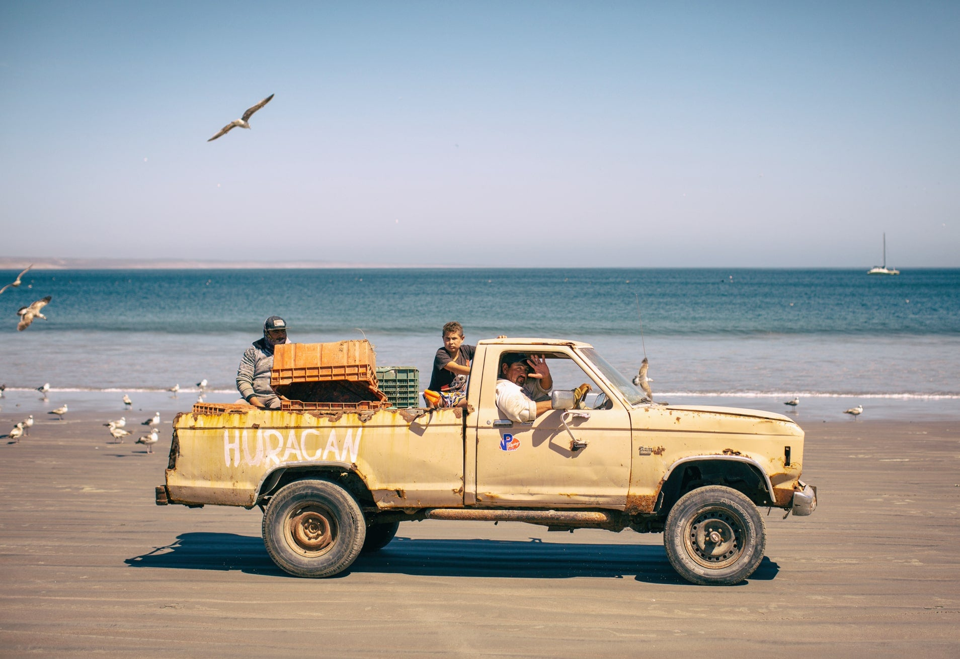 Men driving old truck called Huracan down Mexican beach