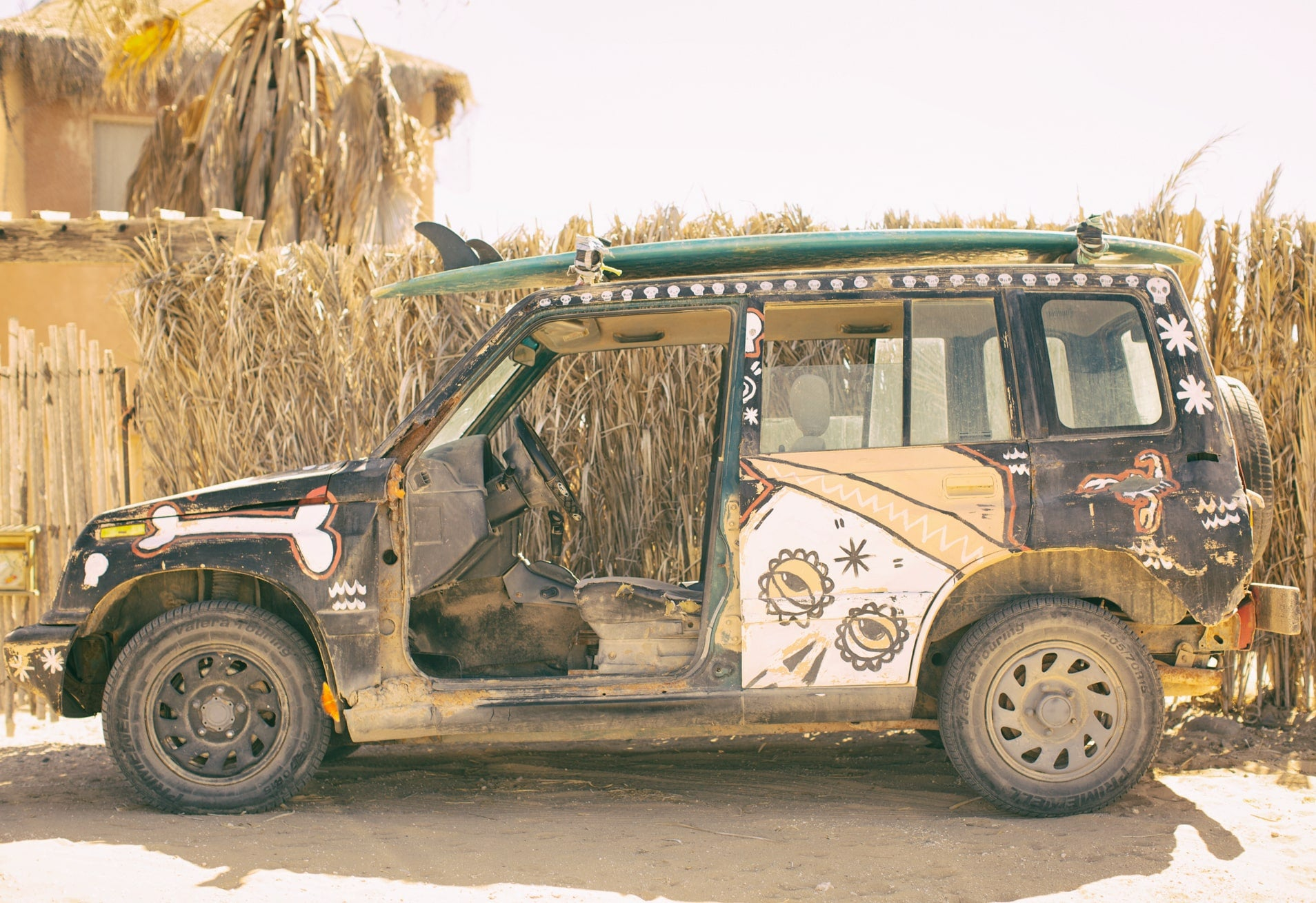 old graffiti painted vehicle with surf board