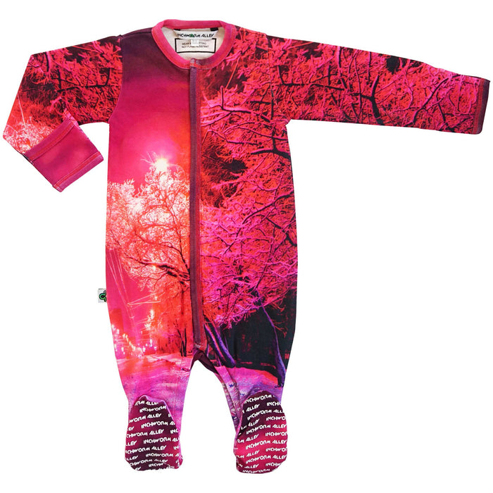Full sleeve footie onesie printed with a snowy city street glowing fuchsia from a street light