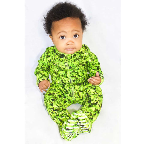 Baby wearing a long sleeve footie with an all-over print of green leaves