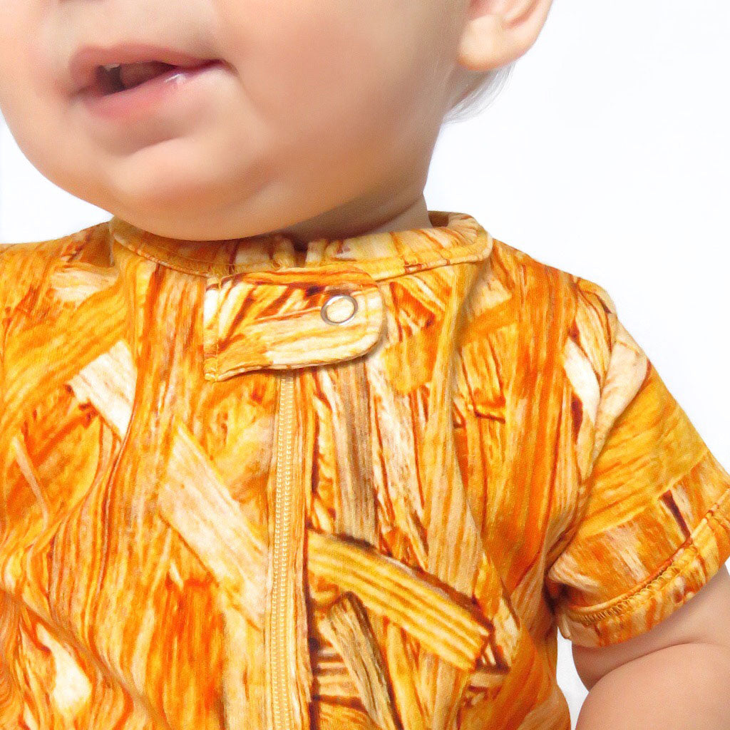 Baby wearing a short sleeve romper with all-over print of wood grain