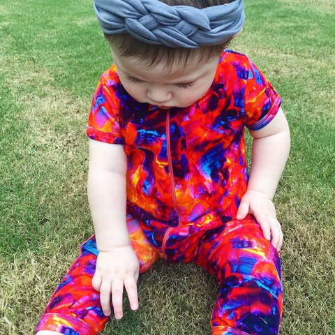 Baby wearing a short sleeve, full leg romper printed with an image of burning coals and embers