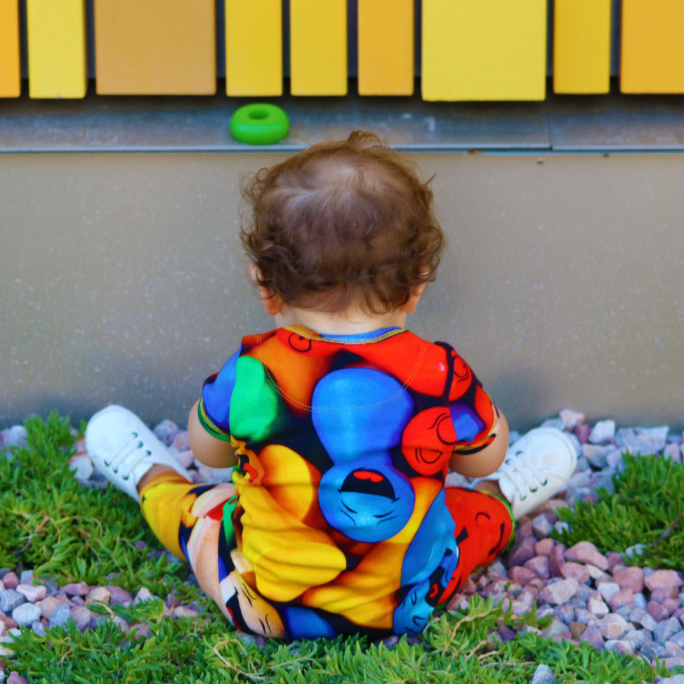Baby wearing a short sleeve, full leg romper with all-over print of multicoloured game pieces