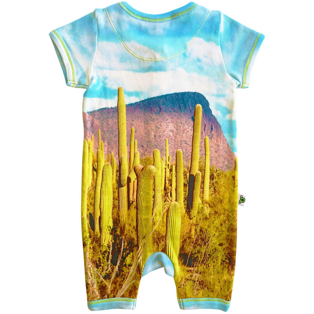 Short sleeve romper with a print of Saguaro cactus set against the backdrop of a craggy mountain and blue sky with white clouds
