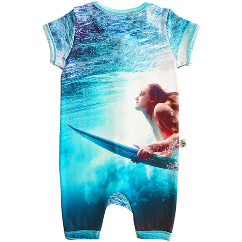Short sleeve romper with a print of a woman in the water on a surfboard in preparation to ride a wave