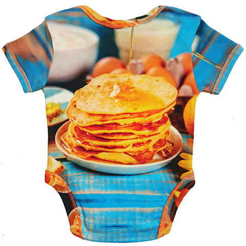 Back view of a short sleeve bodysuit printed with an image of a syrupy stack of pancakes on a breakfast table