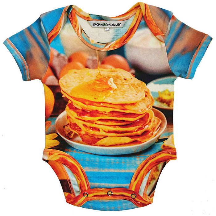 Front view of a short sleeve bodysuit printed with an image of a syrupy stack of pancakes on a breakfast table