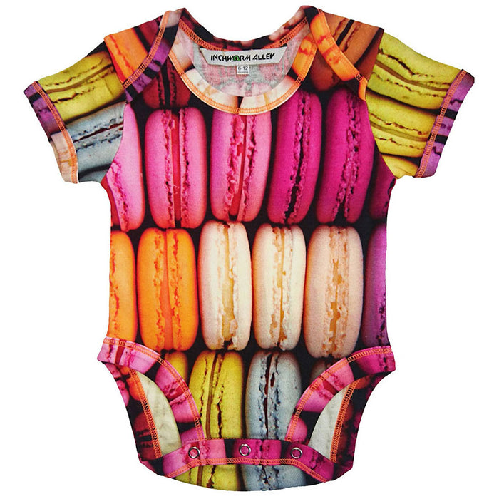 Front view of a short sleeve bodysuit printed with an image of rows of colourful macarons