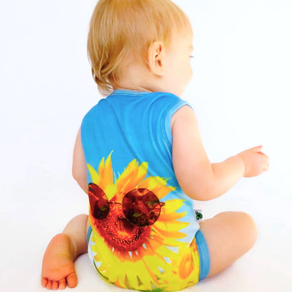 Baby wearing a tank bodysuit with the image of a sunflower wearing sunglasses
