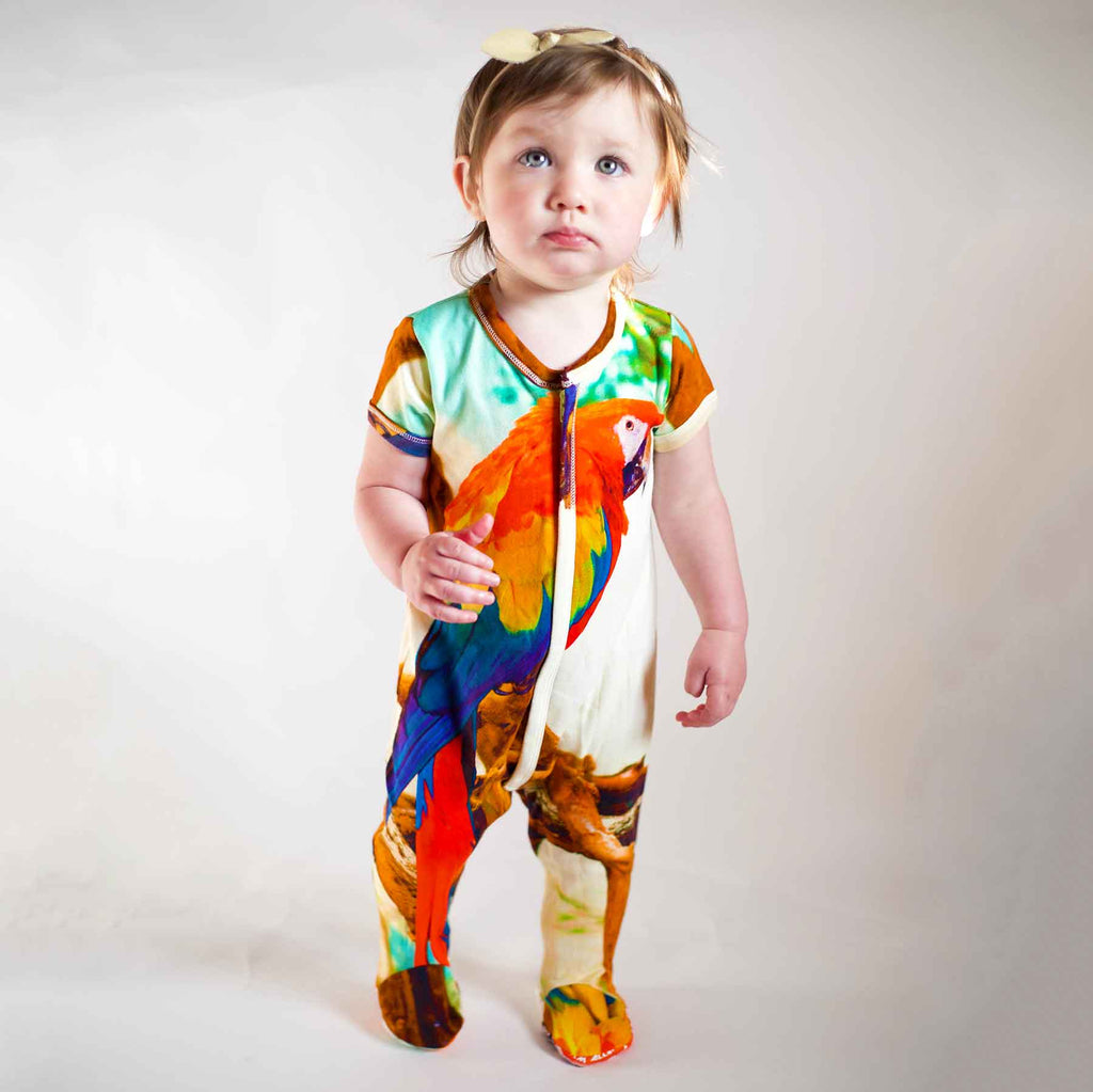 Baby wearing a short sleeve footie printed with a parrot or Macaw with multicolour feathers