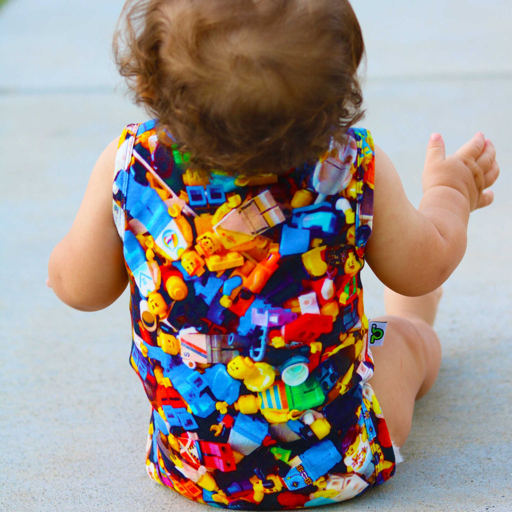 Baby wearing a tank bodysuit with an all-over print of Lego people figurines