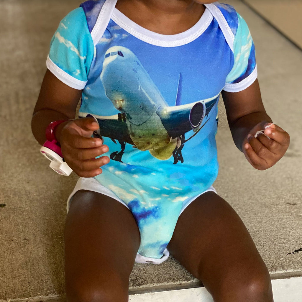 Toddler wearing a short sleeve bodysuit onesie printed with an image of an airplane flying against a blue sky