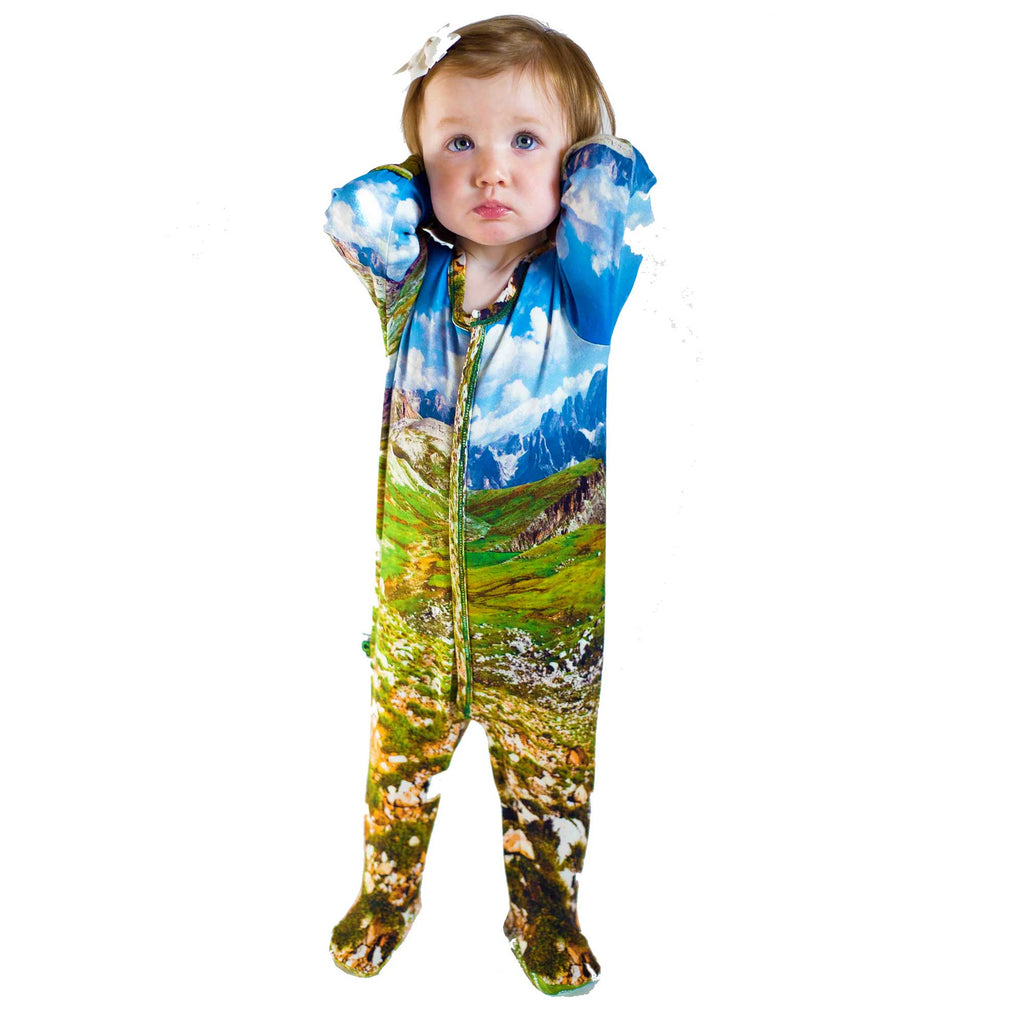 Baby wearing a long sleeve footie with a landscape image of the Alps