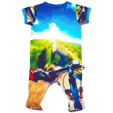 Back view of short sleeve footie with a mountain biker riding at top speed