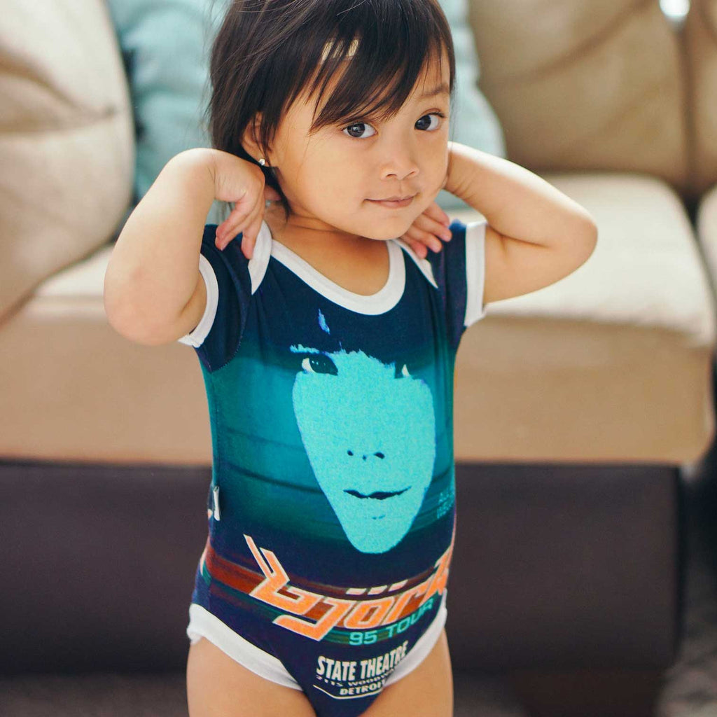 Toddler wearing a short sleeve bodysuit onesie with a print of a retro Bjork poster