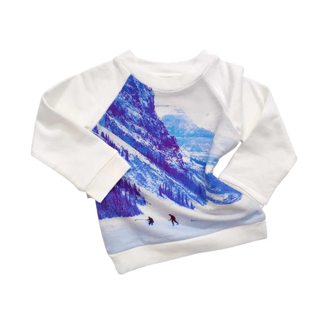 Long sleeve raglan sweatshirt printed with an image of kids playing ice hockey in a snowy, winter landscape against a massive blue mountain