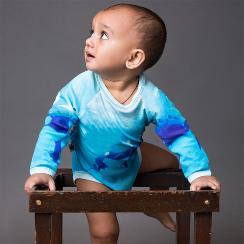 Baby wearing a raglan bodysuit onesie with all-over image of an orca whale and her calf