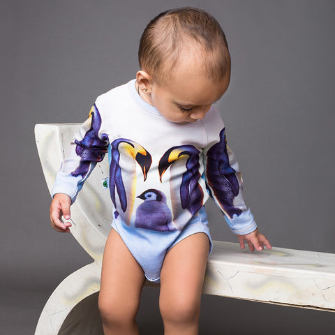 Baby wearing a raglan bodysuit onesie with image of a penguin family