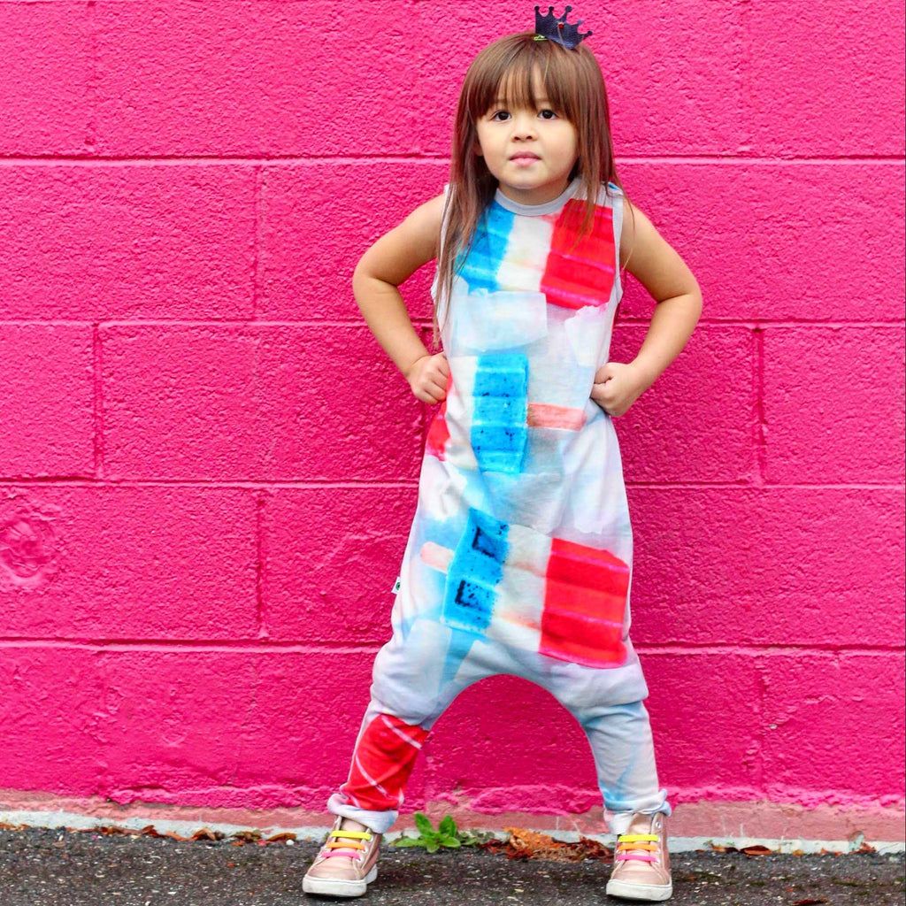 Child wearing a tank jumpsuit with oversized image of tri-colour bomb pops or rocket pops surrounded by ice cubes
