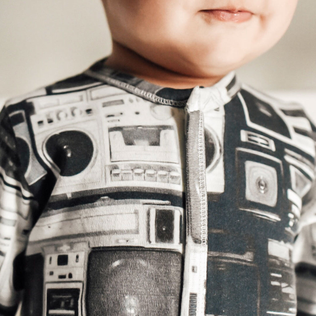 Baby wearing a long sleeve footie printed with a wall of boom boxes in black and white