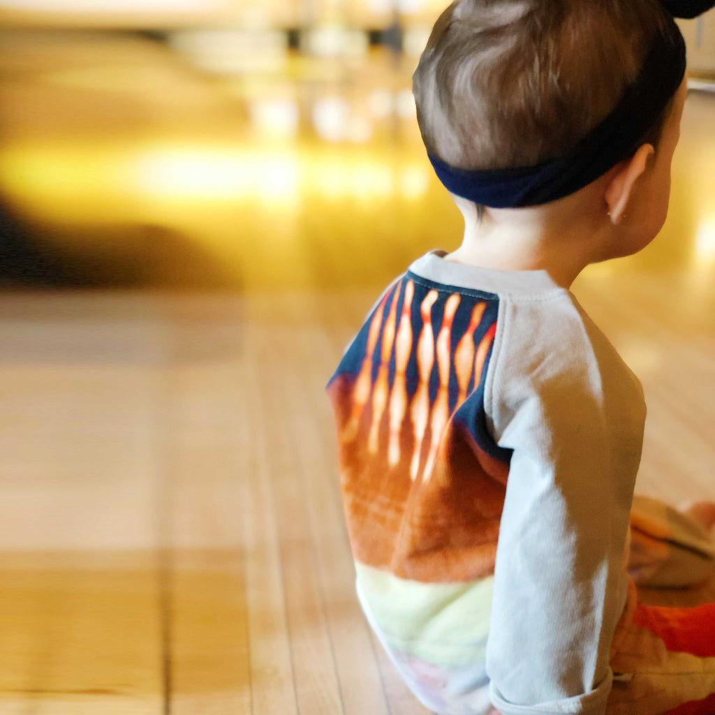 Baby wearing long sleeve raglan romper with print of a bright red bowling ball rolling down a lane towards 10 pins