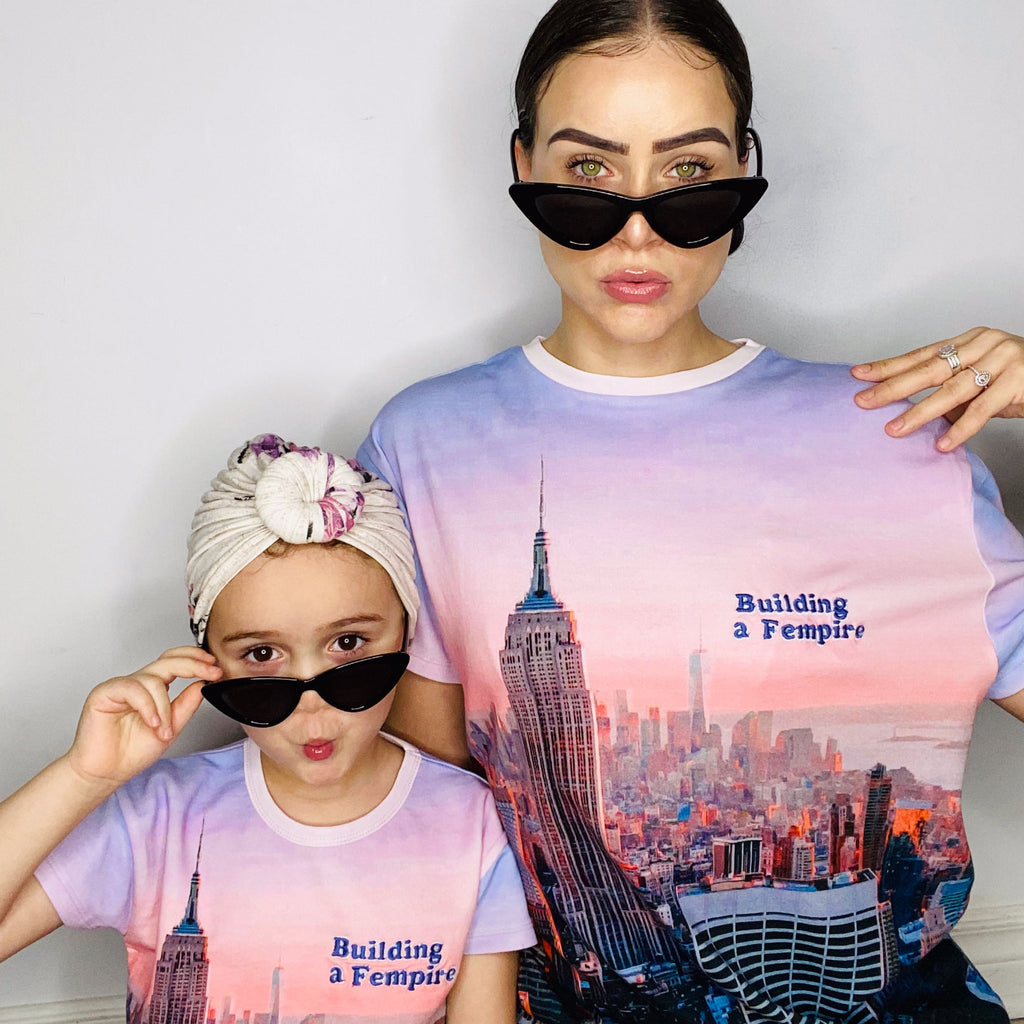 Mother and daughter wearing matching tees with pink/purple pastel image of the Empire State Building and city skyline with the words Building A Fempire
