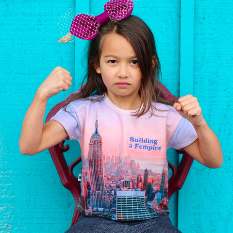 Girl wearing matching tees with a pink/purple pastel image of the Empire State Building and city skyline with the words Building A Fempire