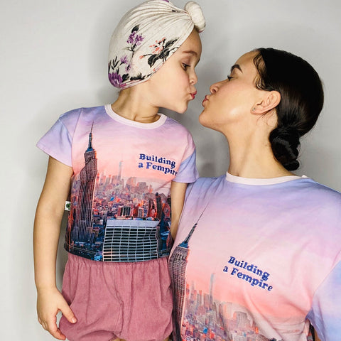 Mother and daughter wearing matching tees with a pink/purple pastel image of the Empire State Building and city skyline with the words Building A Fempire