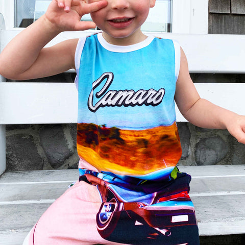 Child wearing a tank jumpsuit with image of a classic Camaro driving down a road and the word Camaro across the chest