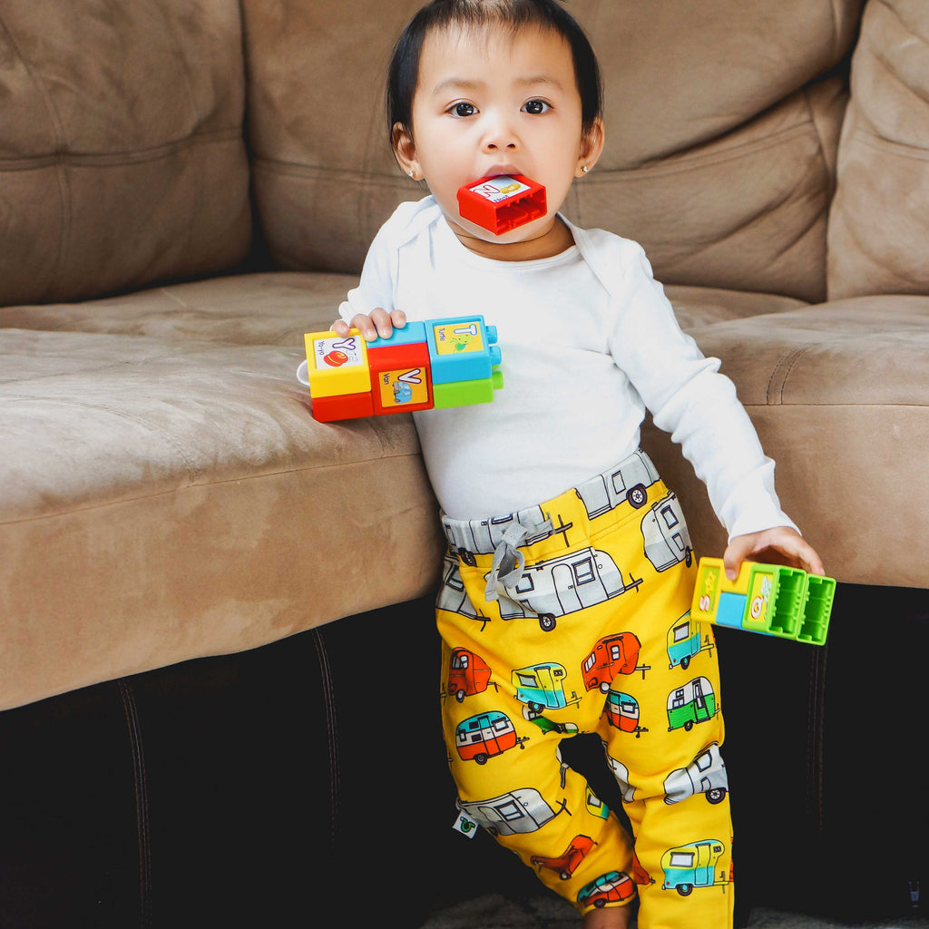 Toddler wearing sweatpants with print of colorful, hand drawn vintage campers