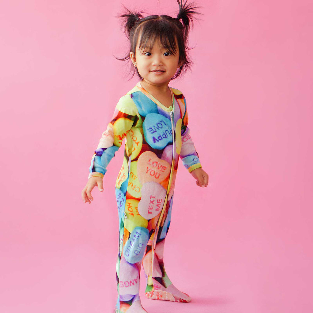 Toddler wearing a full sleeve footie with oversized all over print of candy hearts imprinted with messages
