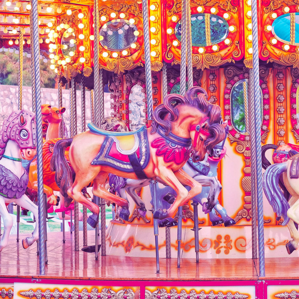 Pink hued image of a carnival carousel horse ride