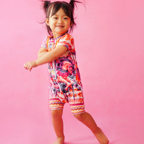Toddler wearing a short sleeve shorts romper with pink hued image of a carnival carousel horse ride
