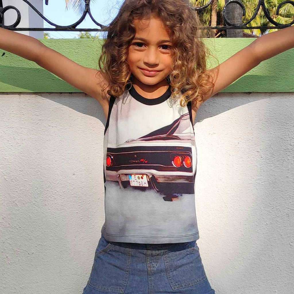Child wearing a tank top with the image of the back-end of a classic Dodge Charger spewing exhaust
