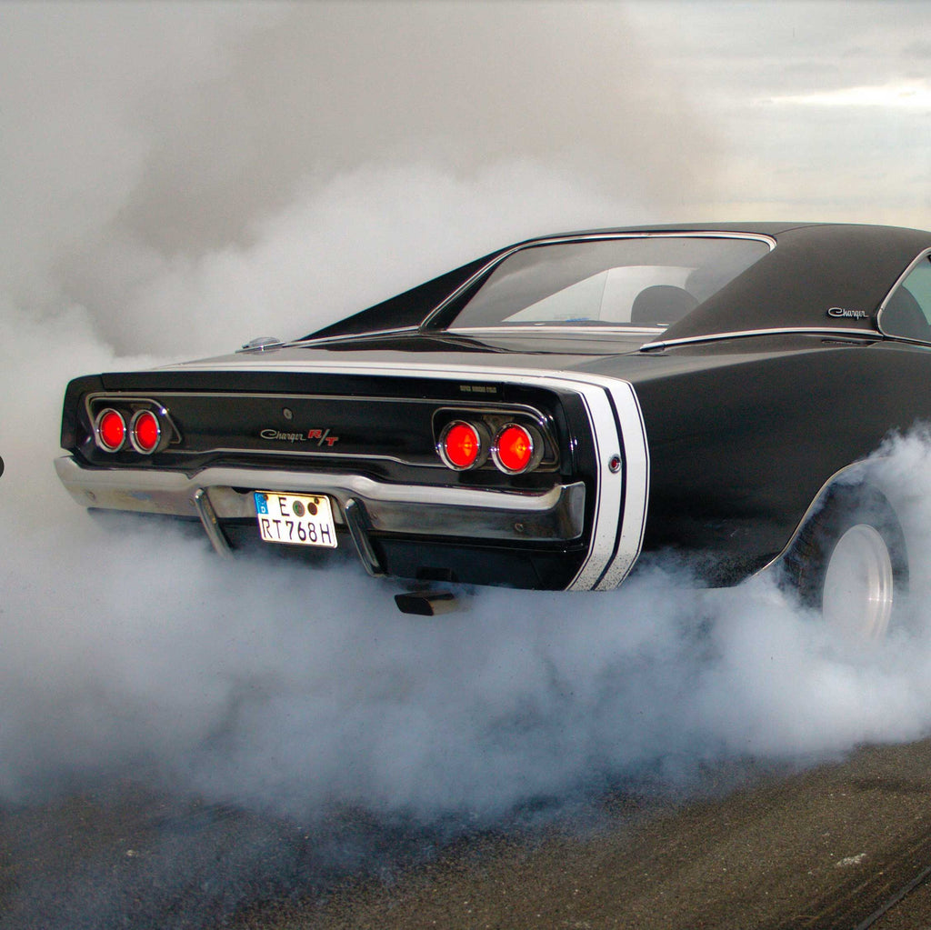 Image of the back-end of a classic Dodge Charger spewing exhaust