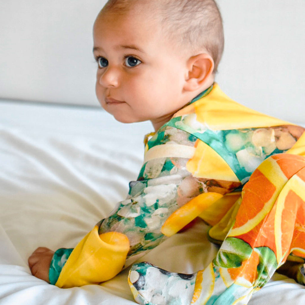 Baby wearing a long sleeve footie with an all-over print of orange popsicles and citrus fruits like mango, orange and lemon slices surrounded by ice cubes