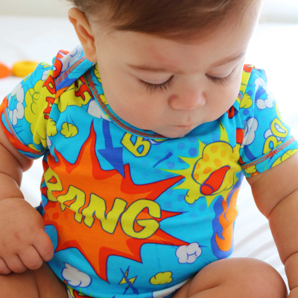 Baby wearing a short sleeve bodysuit with a colourful all-over print of comic bubbles