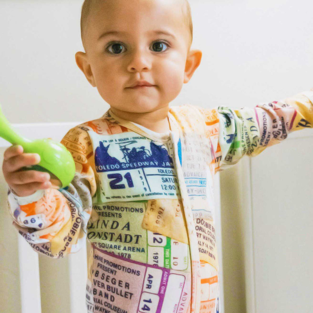 Baby wearing long sleeve footie with an all-over collage of concert ticket stubs from legendary musicians and iconic artists