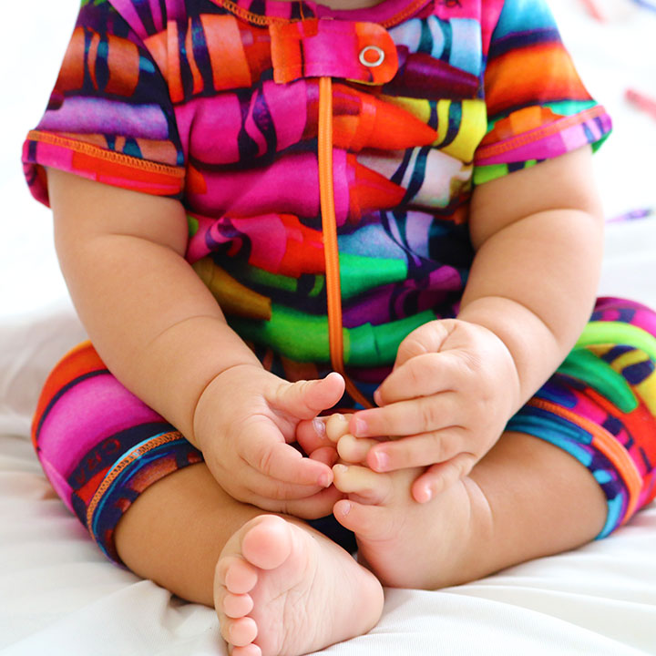 Baby wearing a short sleeve romper with shorts and all-over print of multicoloured crayons