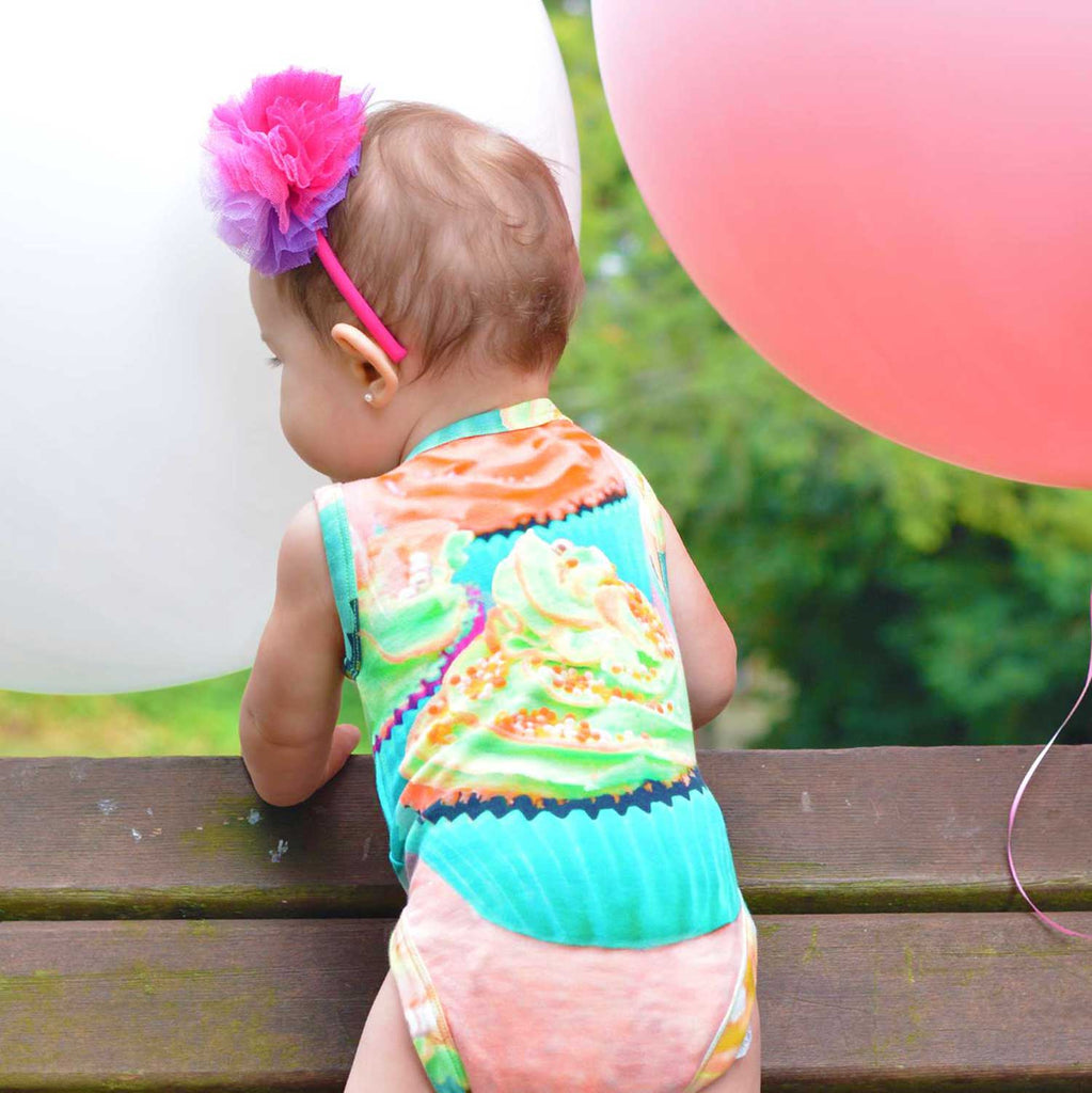 Toddler wearing a tank bodysuit with an image of a frosted cupcake with sprinkles