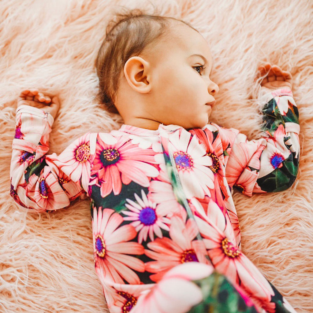 Baby wearing a long sleeve footie with an all-over print of a brightly coloured pink daisies