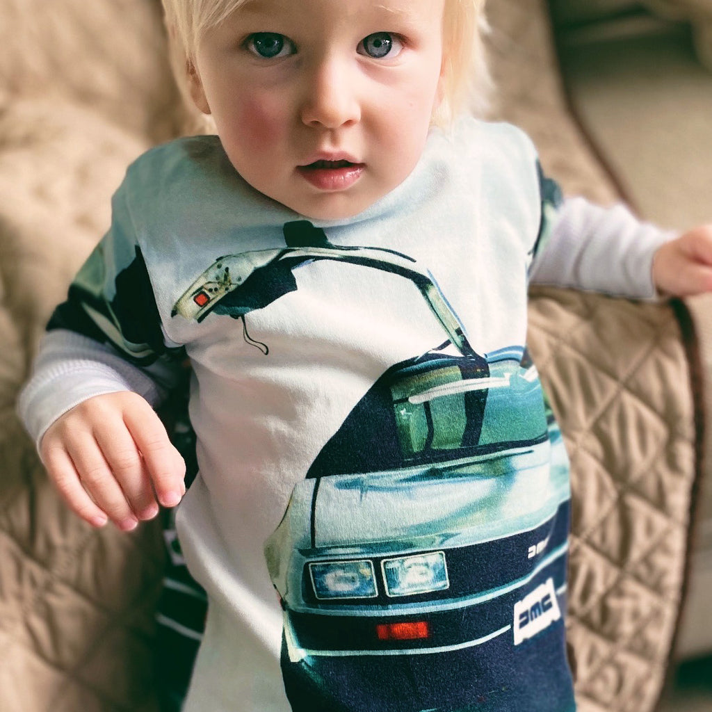 Child wearing a graphic tee with image of the front-end of a Delorean with the doors up