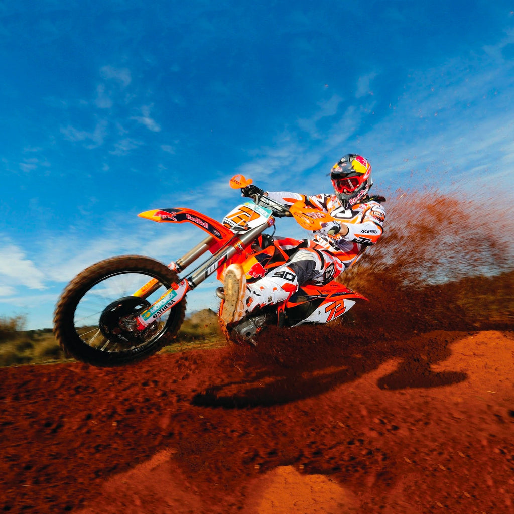 Action shot of a dirt biker tearing over a dirt hill against a blue sky