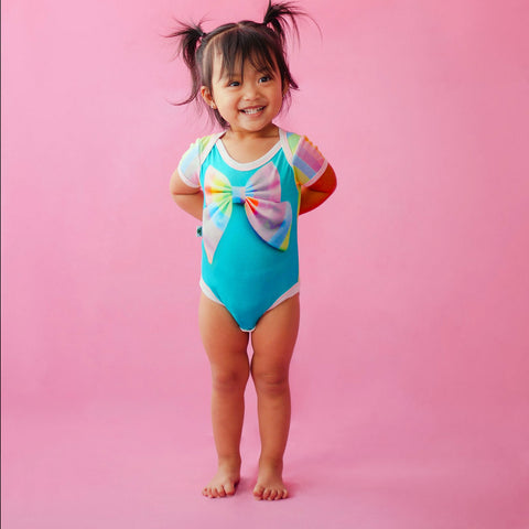 Toddler wearing a short sleeve bodysuit onesie with a tromp l'oeil printed multicolour pastel bow
