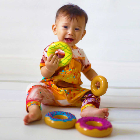Baby wearing a short sleeve romper with all-over print of donuts with sprinkles