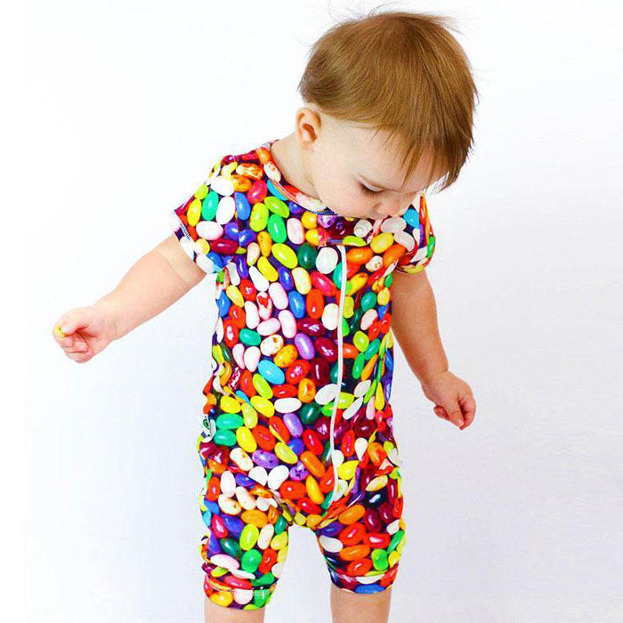Baby wearing a short sleeve romper with shorts and all-over print of multicoloured jelly beans