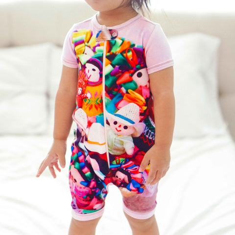 Toddler wearing a short sleeve shorts romper with image of basket of Mexican Marias or colourful rag dolls